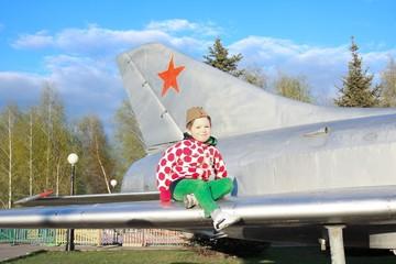 Мальчик в пилотке сидит на крыле самолета