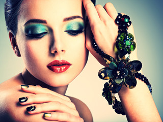 Beautiful woman face with fashion green make-up and jewelry on h
