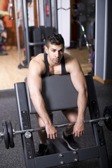 Exhausted man training biceps at gym bench