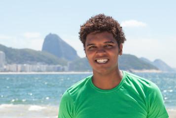 Gut gelaunter Latino im grünen Shirt an der Copacabana