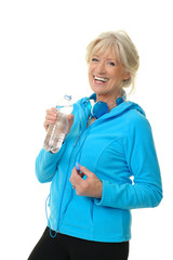 Sportliche Seniorin mit Wasserflasche und Kopfhörer