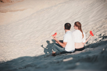 couple sitting back on the beach and are holding watermelon