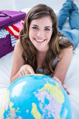 Beautiful woman with a suitcase pointing on a globe