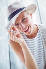 Pretty blonde woman wearing hat and smiling at camera