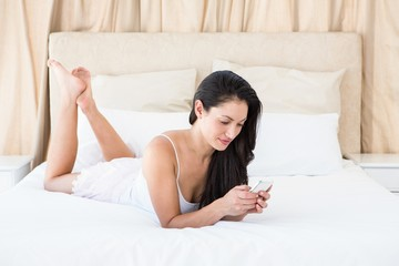 Pretty brunette texting on couch