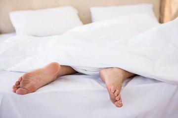 Woman feet under a duvet