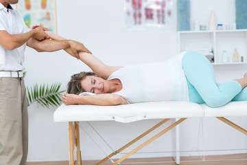Doctor stretching his patients arm