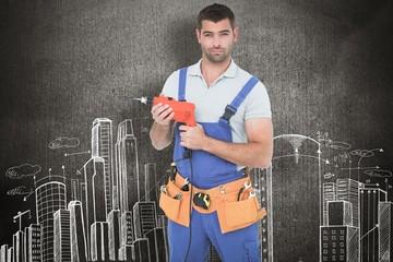 Confident male carpenter in overall holding drill machine