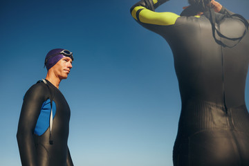 Triathlete standing with his swimming gear on