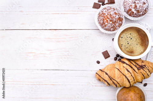 Coffee cup with a croissant and cake . Background.