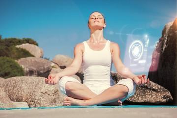 Blonde woman sitting in lotus pose on beach on mat