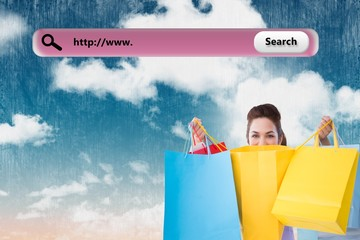 Composite image of happy brunette opening shopping bags