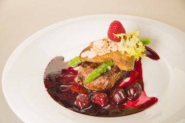 Piece of roasted meat in cherry sauce, asparagus  and raspberry