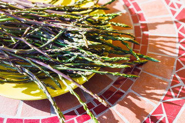 wild asparagus bunch on yellow plate