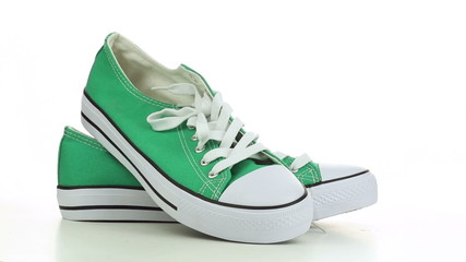 Green sneakers revolve on a white background