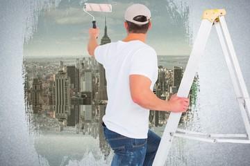 handyman climbing ladder while using paint roller