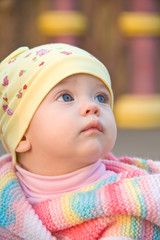 Little girl in bright clothes looking up