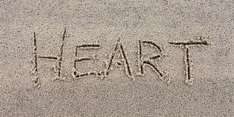 "Inscription ""Heart"" on wet sand."