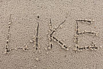 "Inscription ""Like"" on wet sand."