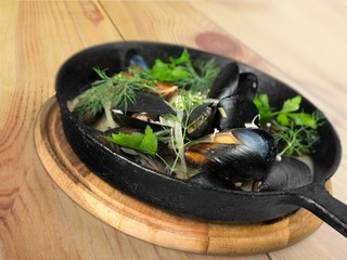Photo. Copper pot of gourmet mussels served on a napkin