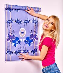 Happy woman glues wallpaper .