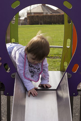 baby on a slide at the park