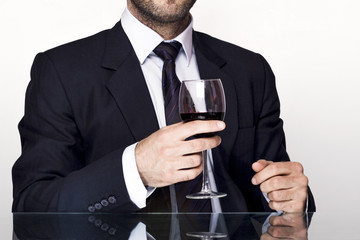 Businessman holding a glass of red wine