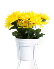 Fake Yellow daisies in white pot.