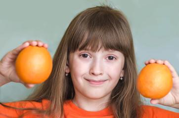Girl holds orange oranges and smiling