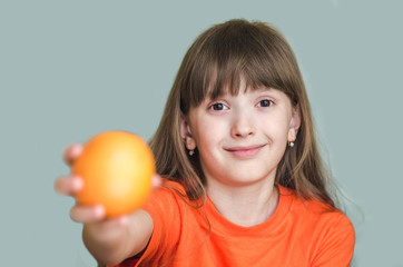 Girl giving orange outstretched arm forward.