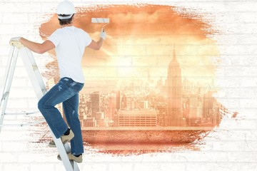 Composite image of man on ladder painting with roller