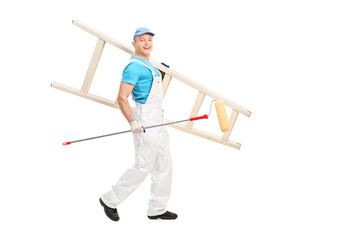 Male painter walking with paint roller and a ladder