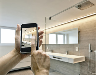 Smarthphone with man hand taking picture in luxury Bathroom