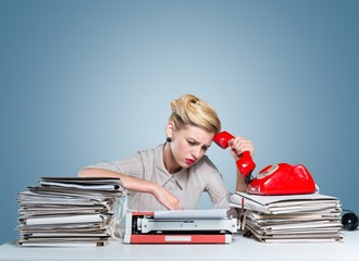 Desk. A bored office worker sitting behind a large stack of