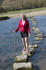 Stepping stones woman crossing river with a stick