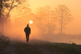 Runner during a foggy, spring sunrise in the countryside.
