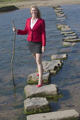 Stepping stones woman crossing river using stick