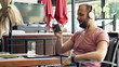 man watching movie on smartphone with headphones sitting in cafe