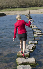 Stepping stones woman crossing river using a stick
