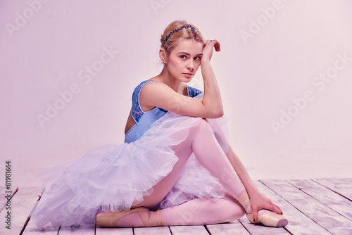 Fotobehang Dance School Tired ballet dancer sitting on the wooden floor