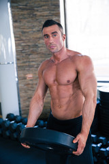 Muscular man holding weight and looking at camera