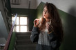girl lights a cigarette in the stairwell - 81982240
