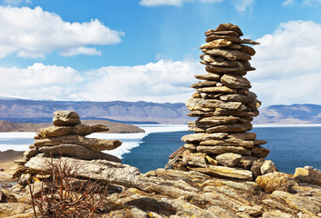 Lake Baikal in spring. Cairns on rocky promontory