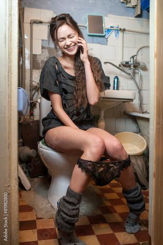 Leinwanddruck Bild girl talking on the phone in the toilet