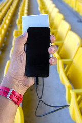 one hand show smartphone with a power bank in sport stadium