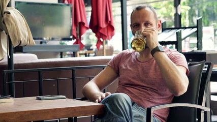 Happy man raising toast to camera and drinking beer in cafe