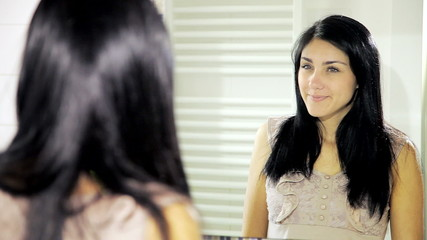 Woman happy about her look in front of mirror smiling