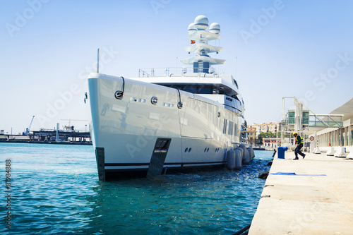 Luxury yacht docking at port. - 81984888