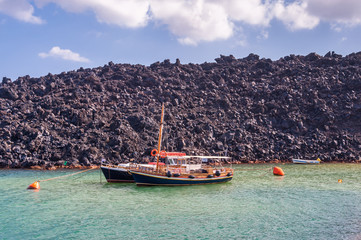Boats moored to large boulders of lava