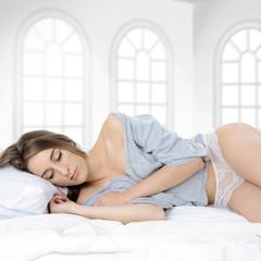 Frau in Dessous schläft im Bett